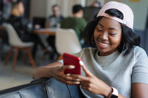 Mulher negra alegre mandando mensagem de texto para a amiga