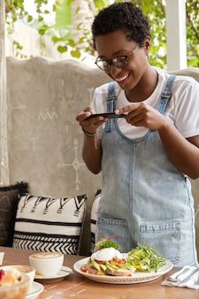 Mulher negra alegre tira foto de comida exótica em cafeteria, bebe café com leite
