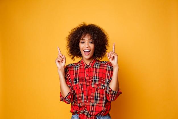 Mulher negra americana alegre na camisa vermelha que olha para cima e que aponta os dedos acima no espaço da cópia isolado sobre o fundo alaranjado.