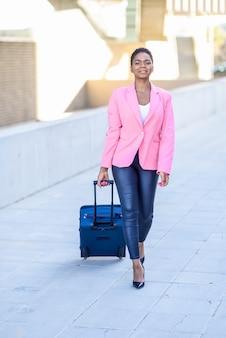 Mulher negra andando com mala de viagem, vestindo jaqueta rosa.