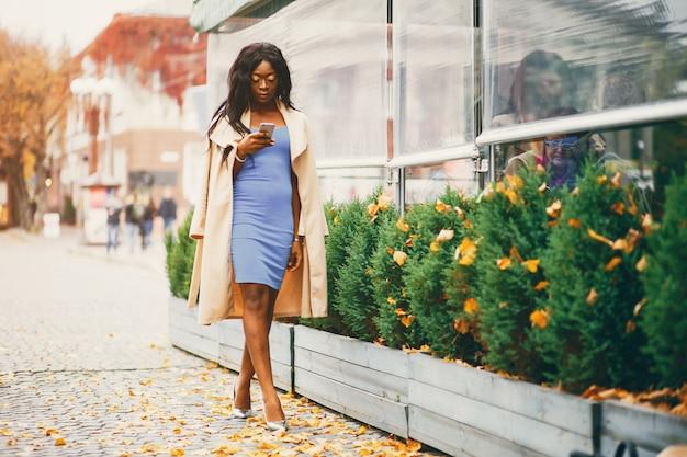 Mulher negra andando em uma cidade de outono
