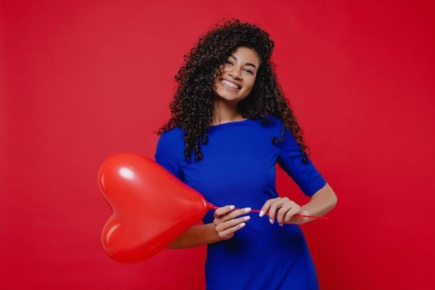 Mulher negra animada com balão em forma de coração com vestido azul na parede vermelha