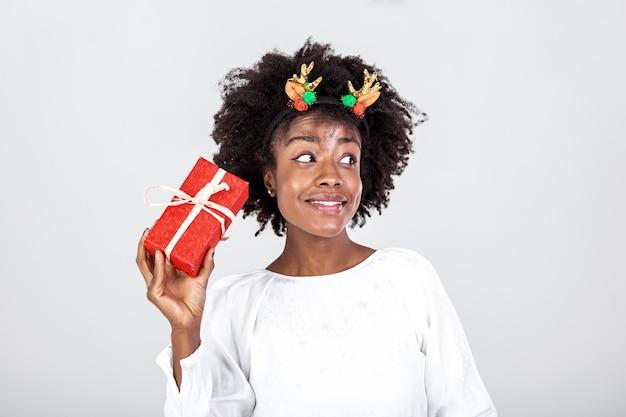 Mulher negra animada sacudindo uma caixa de presente embrulhada recebendo presentes em seu aniversário ou em pé de natal