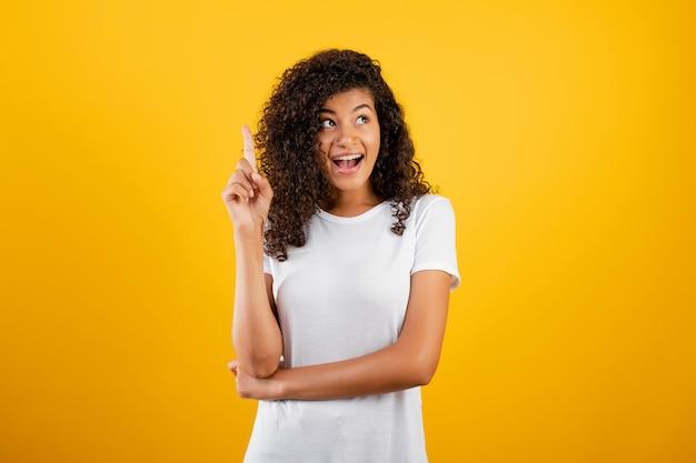 Mulher negra animada, tendo uma idéia, apontando o dedo isolado sobre amarelo
