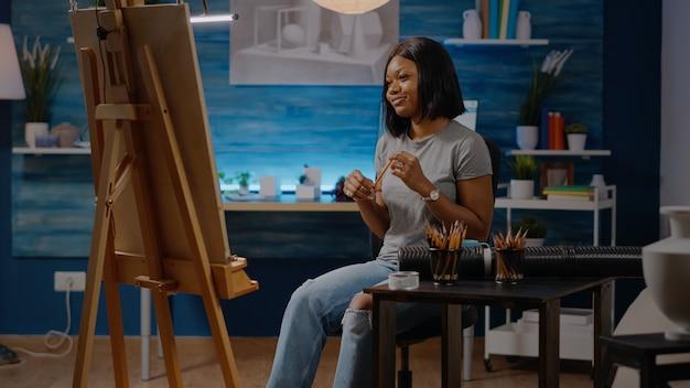 Mulher negra artista sentada no estúdio com tela e cavalete