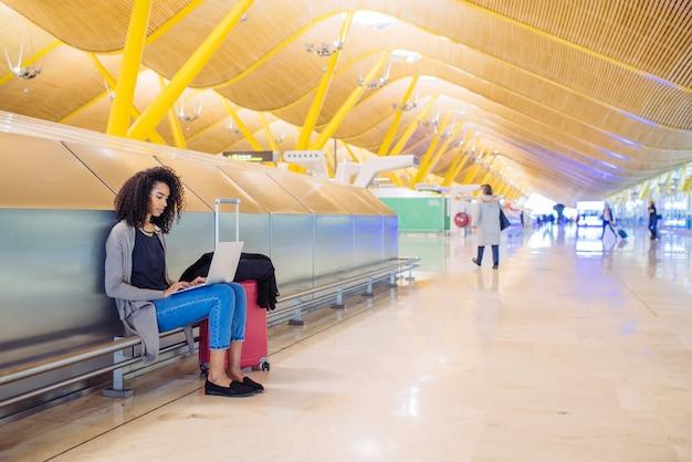 Mulher negra atraente no aeroporto sentado e trabalhando com o laptop
