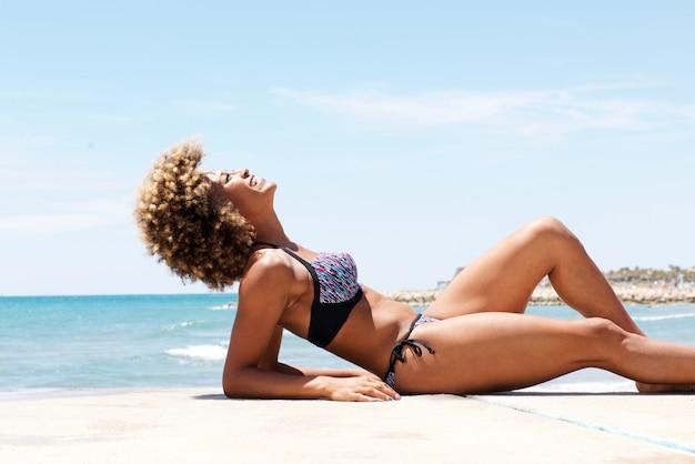 Mulher negra atrativa que encontra-se na praia e sunbathing
