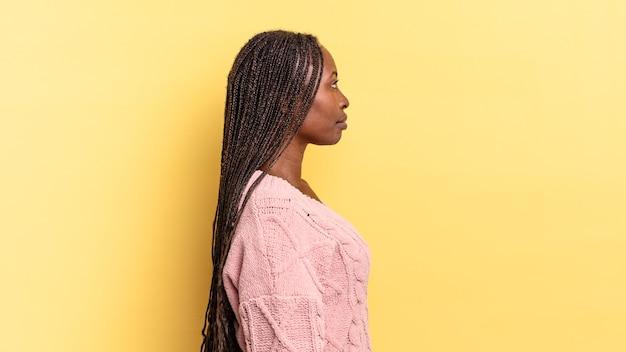 Mulher negra bonita afro em vista de perfil olhando para copiar o espaço à frente, pensando, imaginando ou sonhando acordado