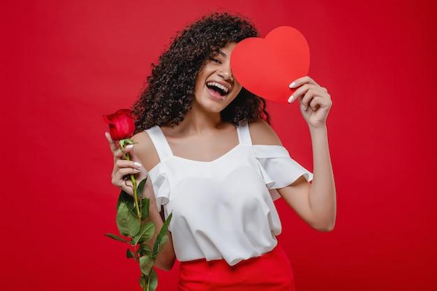 Mulher negra bonita, cobrindo os olhos com cartão em forma de coração e segurando rosa isolada sobre vermelho