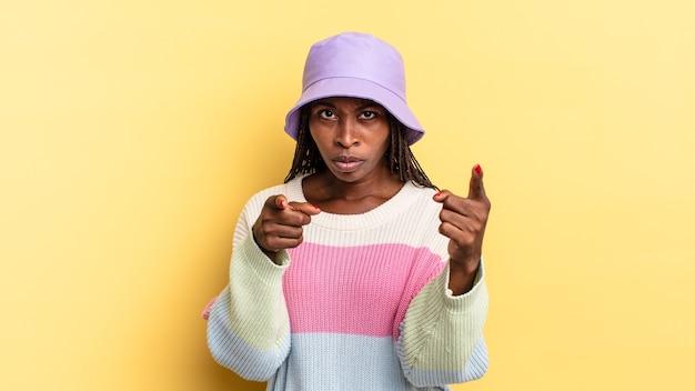 Mulher negra bonita e negra apontando para a câmera com os dois dedos e uma expressão raivosa, dizendo para você cumprir seu dever