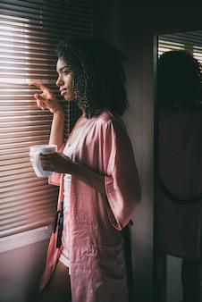 Mulher negra bonita em pé na janela com uma xícara de café
