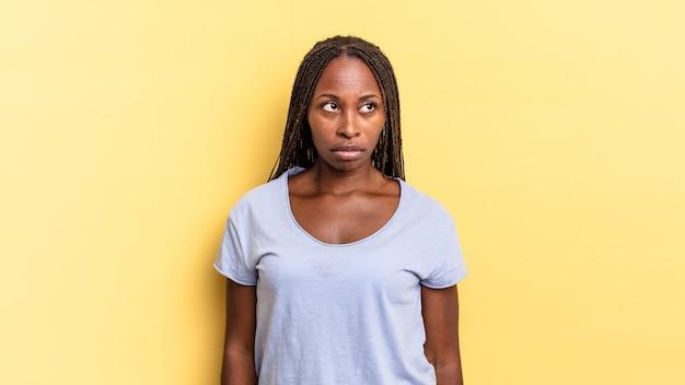Mulher negra bonita negra se sentindo triste, chateada ou com raiva e olhando para o lado com uma atitude negativa, franzindo a testa em desacordo