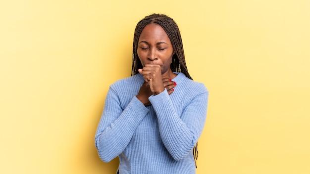 Mulher negra bonita, negra, sentindo-se mal, com dor de garganta e sintomas de gripe, tosse com a boca coberta