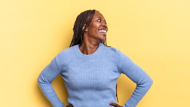 Mulher negra bonita parecendo feliz, alegre e confiante, sorrindo com orgulho e olhando para o lado com as duas mãos na cintura
