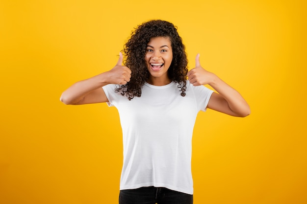Mulher negra bonita sorrindo e mostrando os polegares isolados sobre amarelo