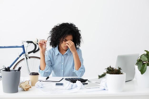 Mulher negra cansada com óculos nas mãos esfregando os olhos, cheia de pensamentos tristes e inquietos