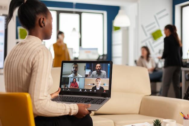Mulher negra cansada falando com um colega usando videochamada segurando um smartphone com fone de ouvido sem fio, sentada no sofá no escritório