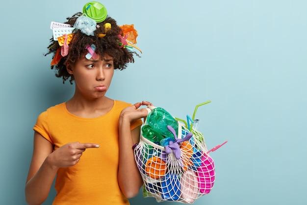 Mulher negra chateada tem cabelo encaracolado, aponta o dedo da frente para o lixo de plástico, limpa o lixo, faz projeto ambiental, está desanimada, usa camiseta laranja, fica de pé sobre a parede azul