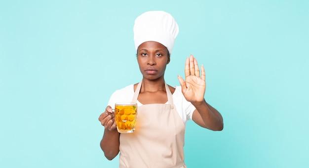 Mulher negra chef adulta afro-americana com um litro de cerveja