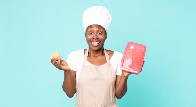 Mulher negra chef adulta afro-americana com um tupperware Foto Premium