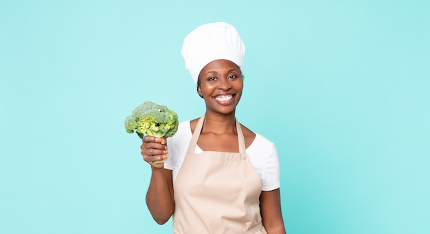 Mulher negra chef adulta segurando um brócolis