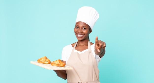 Mulher negra chef adulta segurando uma bandeja de croissants