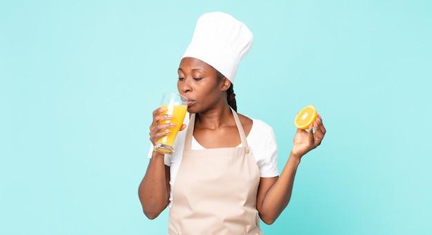 Mulher negra chef adulto americano africano. conceito de suco de laranja