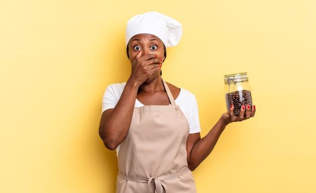 Mulher negra chef afro cobrindo a boca com as mãos com uma expressão chocada e surpresa, mantendo um segredo ou dizendo oops. conceito de grãos de café