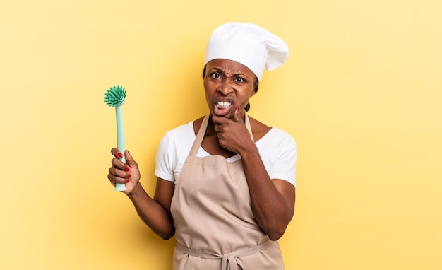 Mulher negra chef afro com boca e olhos bem abertos e mão no queixo, sentindo-se desagradavelmente chocada, dizendo o quê ou uau. conceito de limpeza de pratos