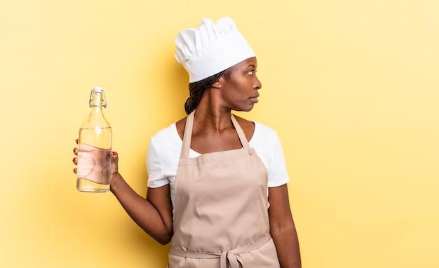 Mulher negra chef afro em vista de perfil, olhando para copiar o espaço à frente, pensando, imaginando ou sonhando segurando uma garrafa de água