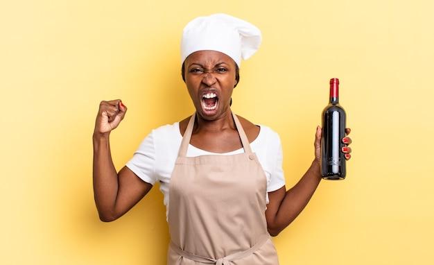 Mulher negra chef afro gritando agressivamente com uma expressão de raiva ou com os punhos cerrados celebrando o sucesso. conceito de garrafa de vinho