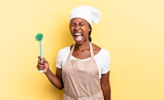 Mulher negra chef afro gritando agressivamente, parecendo muito zangada, frustrada, indignada ou irritada, gritando não. conceito de limpeza de pratos