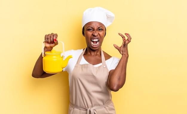 Mulher negra chef afro gritando com as mãos no ar, sentindo-se furiosa, frustrada, estressada e chateada. conceito de bule
