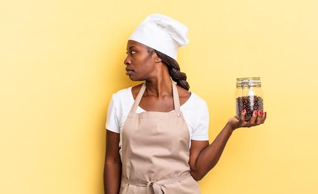 Mulher negra chef afro na vista de perfil, olhando para copiar o espaço à frente, pensando, imaginando ou sonhando acordado. conceito de grãos de café