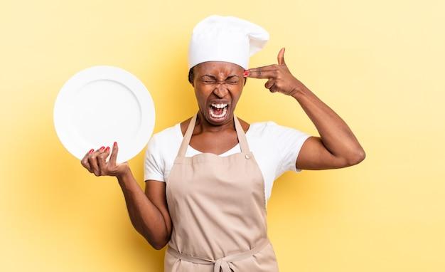Mulher negra chef afro olhando infeliz e estressada, gesto de suicídio fazendo sinal de arma com a mão, apontando para a cabeça. conceito de prato vazio