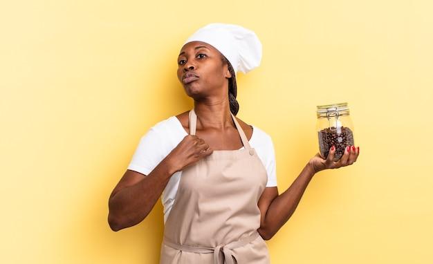 Mulher negra chef afro parecendo arrogante, bem-sucedida, positiva e orgulhosa, apontando para si mesma. conceito de grãos de café