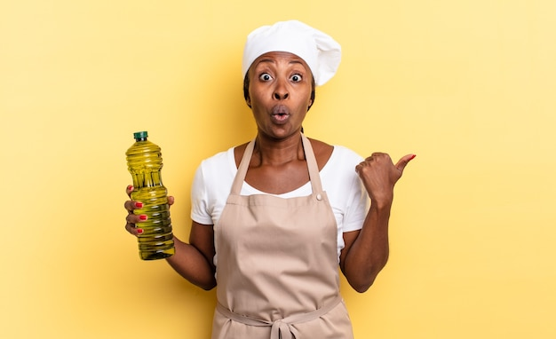 Mulher negra chef afro parecendo espantada com a descrença, apontando para o objeto ao lado e dizendo uau, inacreditável. conceito de azeite