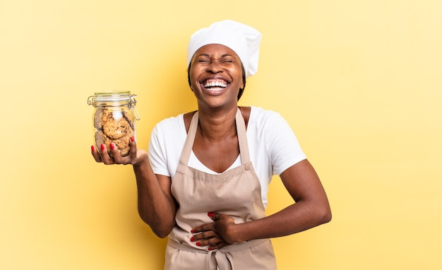 Mulher negra chef afro rindo alto de uma piada hilária, sentindo-se feliz e alegre, se divertindo. conceito de biscoitos