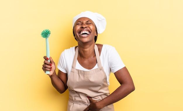 Mulher negra chef afro rindo alto de uma piada hilária, sentindo-se feliz e alegre, se divertindo. conceito de limpeza de pratos