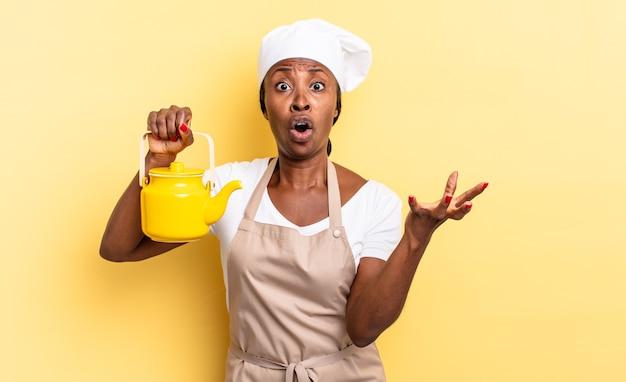 Mulher negra chef afro se sentindo extremamente chocada e surpresa, ansiosa e em pânico, com um olhar estressado e horrorizado. conceito de bule