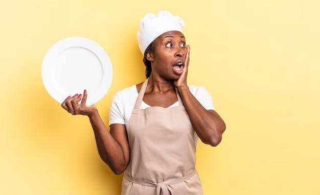 Mulher negra chef afro se sentindo feliz, animada e surpresa, olhando para o lado com as duas mãos no rosto. conceito de prato vazio