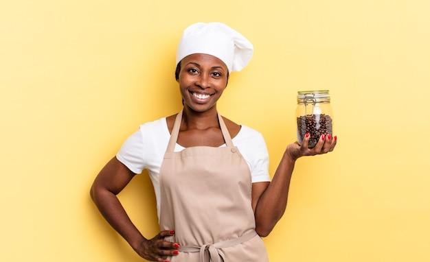 Mulher negra chef afro sorrindo alegremente com uma mão no quadril e atitude confiante, positiva, orgulhosa e amigável. conceito de grãos de café