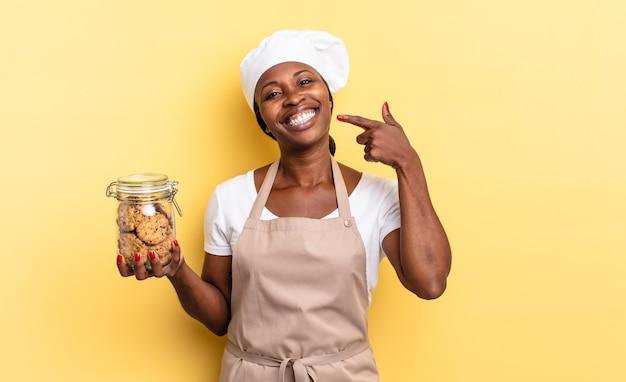 Mulher negra chef afro sorrindo com confiança, apontando para o próprio sorriso largo, atitude positiva, relaxada e satisfeita. conceito de biscoitos