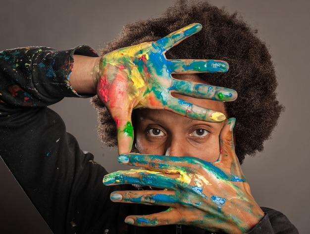 Mulher negra com as mãos pintadas em cinza