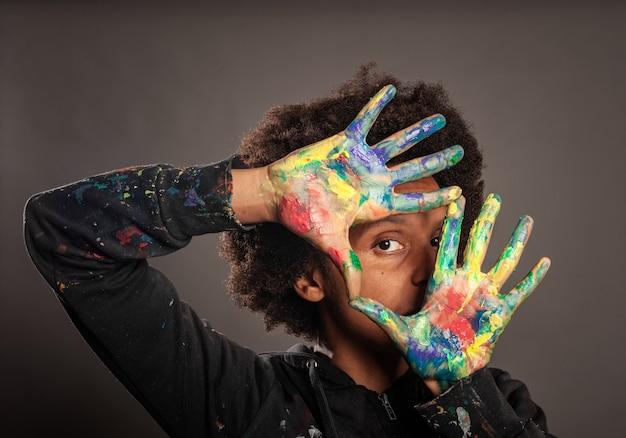 Mulher negra com as mãos pintadas
