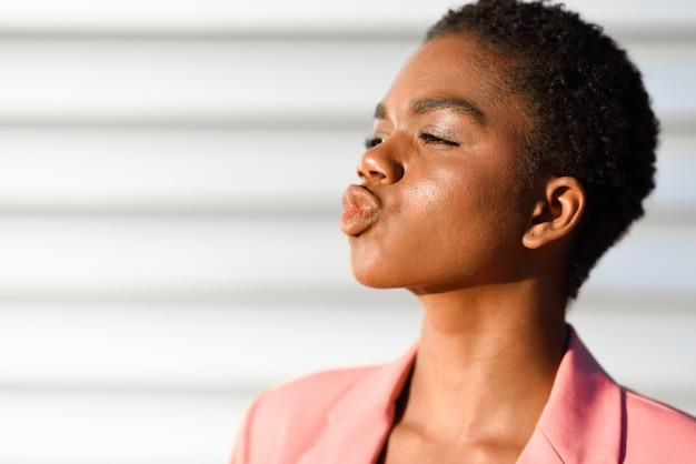 Mulher negra, com cabelo muito curto mandando um beijo.