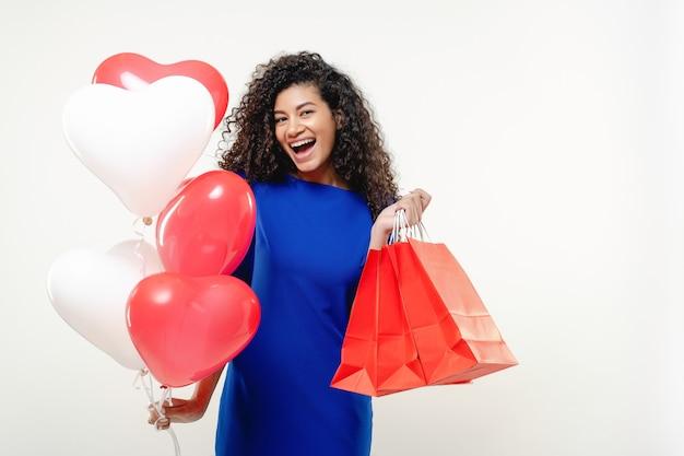 Mulher negra com coração em forma de balões coloridos e sacolas vermelhas isoladas na parede branca