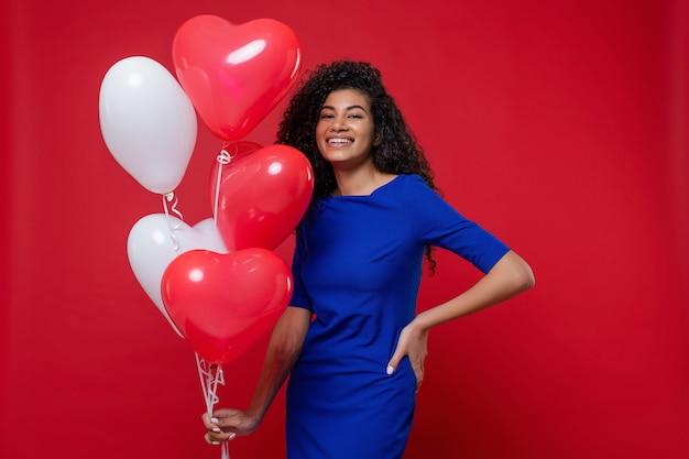 Mulher negra com coração em forma de balões coloridos, vestido azul na parede vermelha