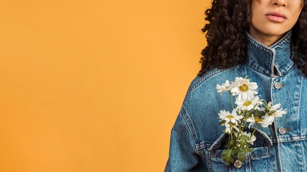 Mulher negra com flores no bolso do casaco