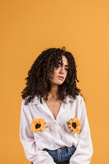 Mulher negra com flores nos bolsos da camisa